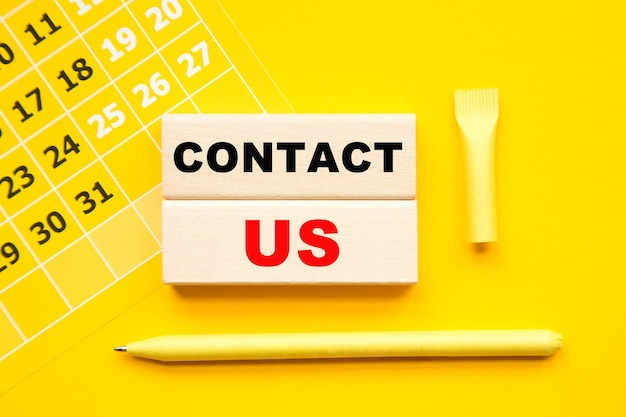 Contactez-nous inscription sur cubes, calendrier abstrait, stylo jaune sur fond jaune