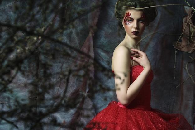 Conte de fée. théâtre. femme en robe rouge. coiffure et maquillage fantastiques. fantaisie.