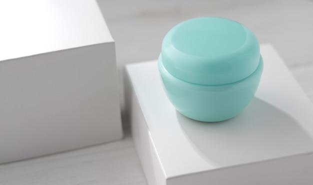 Contenant de crème hydratante bleue sur boîte cubique blanche