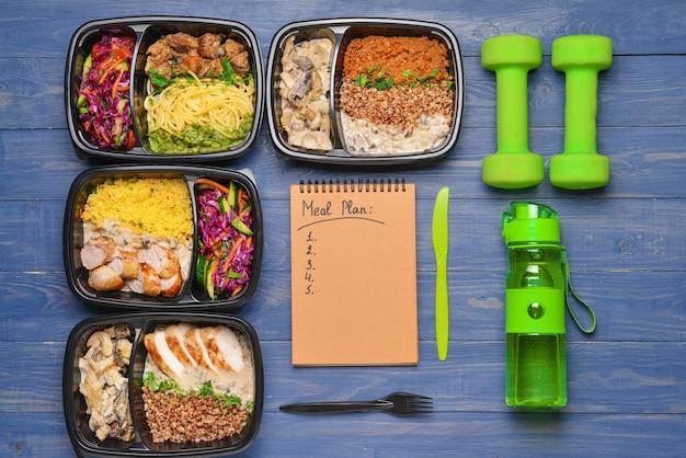 Contenants avec des aliments sains, une bouteille d'eau, des haltères et un plan de repas sur la couleur