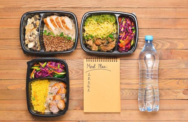 Contenants avec des aliments sains, une bouteille d'eau et un plan de repas sur bois