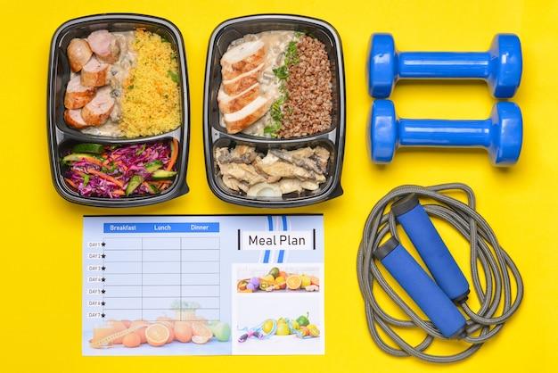 Contenants avec des aliments sains, des équipements sportifs et un plan de repas sur la couleur
