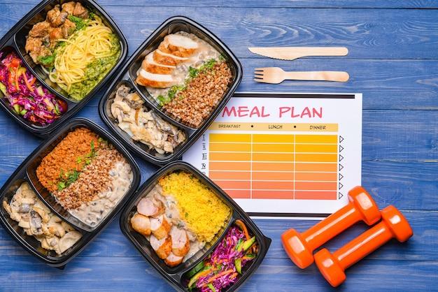 Contenants avec des aliments sains, des haltères et un plan de repas sur la couleur
