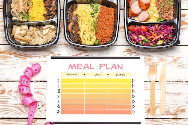 Contenants avec des aliments sains, ruban à mesurer et plan de repas sur bois