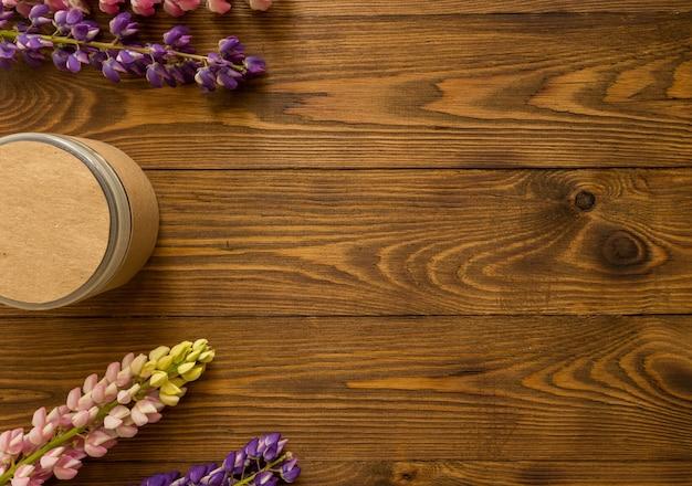Contenants de bouteilles cosmétiques avec des fleurs de lupin à base de plantes et une étiquette vierge pour la maquette de marque pour les produits écologiques naturels