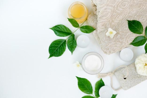 Contenants de cosmétiques avec des herbes vertes feuilles sur blanc