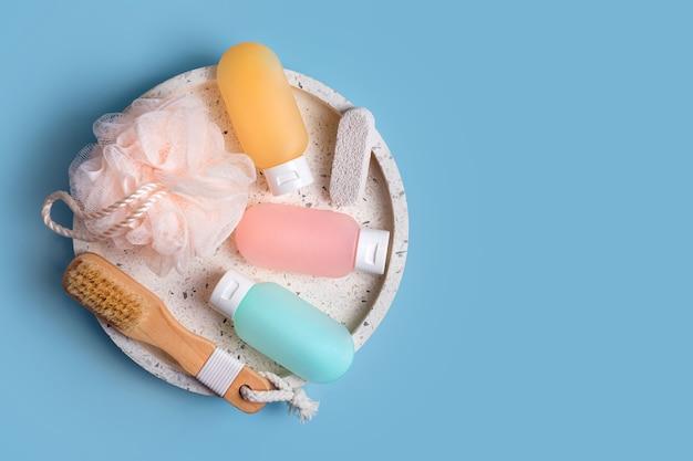 Contenants en plastique colorés pour shampoing, baume capillaire et gel douche avec des débarbouillettes sur un plateau en marbre. produits cosmétiques pour spa et accessoires de bain sur fond bleu