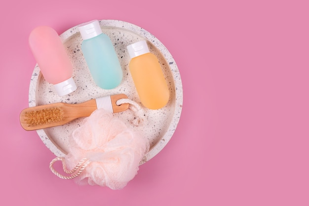Contenants en plastique colorés pour shampoing, baume capillaire et gel douche avec des débarbouillettes sur un plateau en marbre. produits cosmétiques pour spa et accessoires de bain sur fond rose