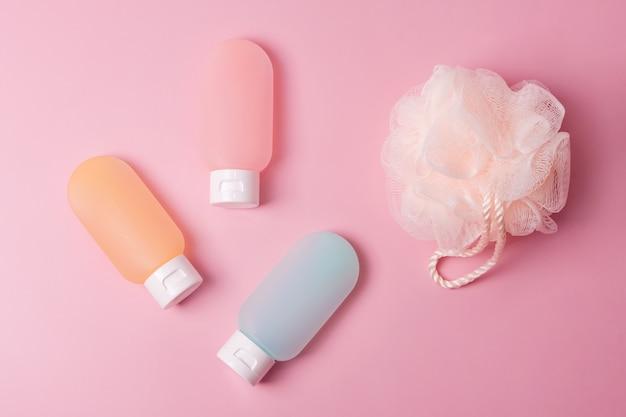 Contenants en plastique colorés pour shampoing, baume capillaire et gel douche avec débarbouillettes. produits cosmétiques pour spa et accessoires de bain sur fond rose