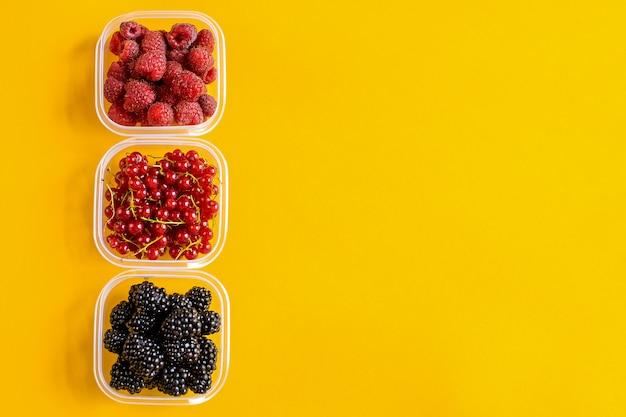 Contenants en plastique avec framboises, mûres et cerises