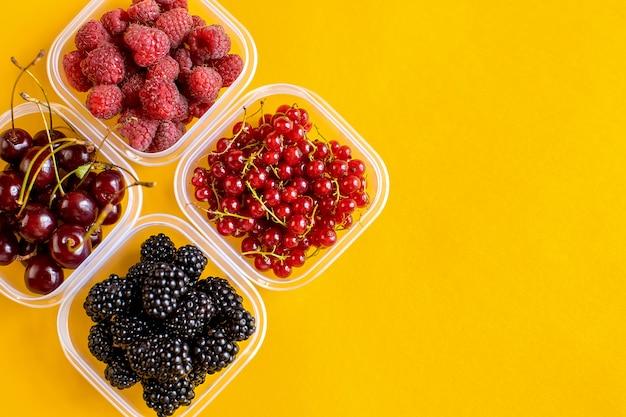 Contenants en plastique avec framboises, mûres, groseilles rouges et cerises