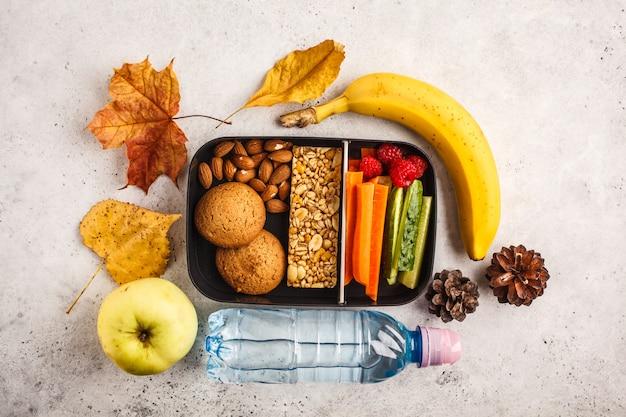 Contenants de préparation de repas sains à l'école avec barre de céréales, fruits, légumes et collations. plats à emporter sur fond blanc, vue de dessus.