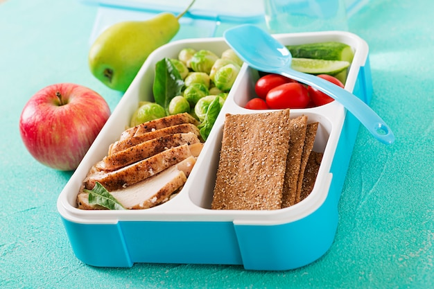 Contenants de préparation de repas verts sains avec filet de poulet, riz, choux de bruxelles et légumes
