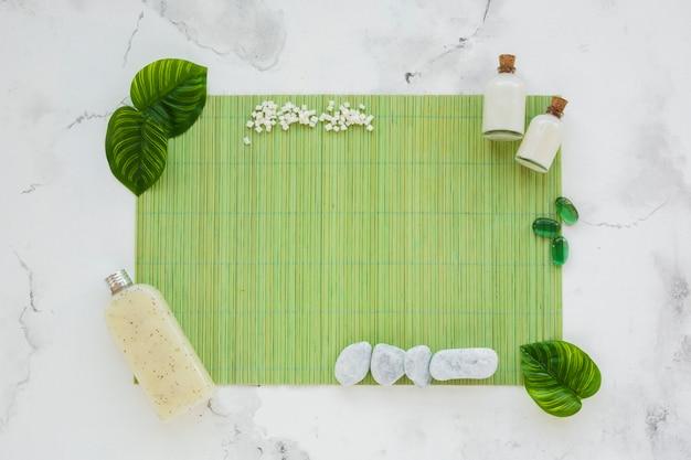 Contenants avec des produits sur tapis vert