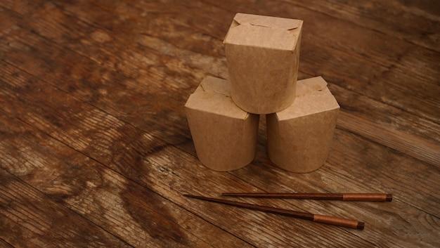 Conteneur alimentaire en carton de papier brun sur fond en bois. livraison de plats asiatiques. emballage wok