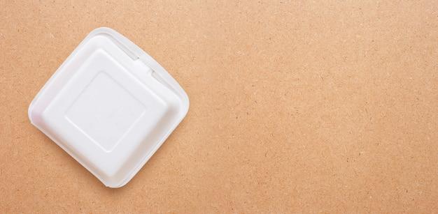 Conteneur alimentaire en mousse sur fond de contreplaqué.