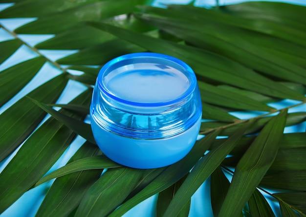 Conteneur bleu avec crème pour le visage ou le corps sur la feuille de palmier