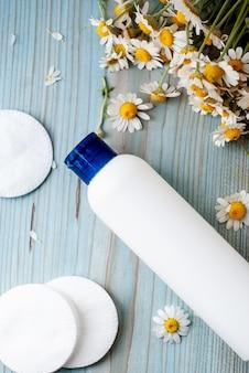 Conteneur de bouteille blanche avec des fleurs de camomille à base de plantes.