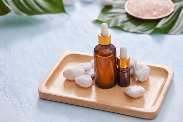 Conteneur de bouteille de soins cosmétiques naturels et feuille verte biologique, ingrédients de fleurs avec la verrerie de laboratoire sur fond blanc. remède fait maison et concept de produit de beauté.