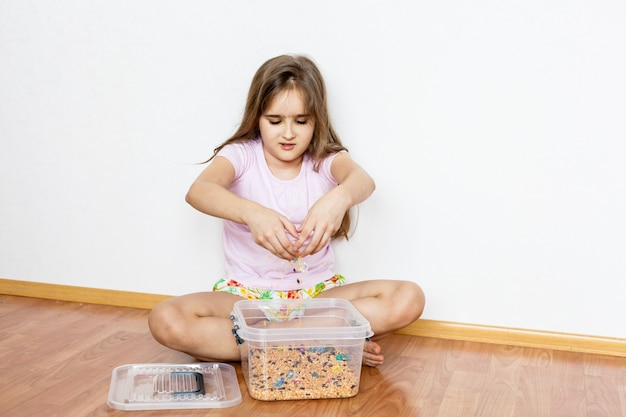 Conteneur de céréales, matériaux pour le développement des enfants, motricité fine, logique et mémoire, esprit, fille se développe, jeux avec du sable, développement de l'enfant, enfance, préparation à l'école, montessori