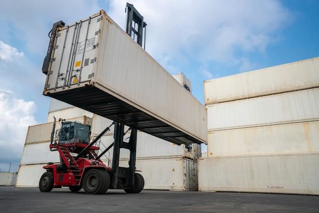 Conteneur de fret pour l'expédition à l'étranger dans un chantier naval avec une machine lourde.
