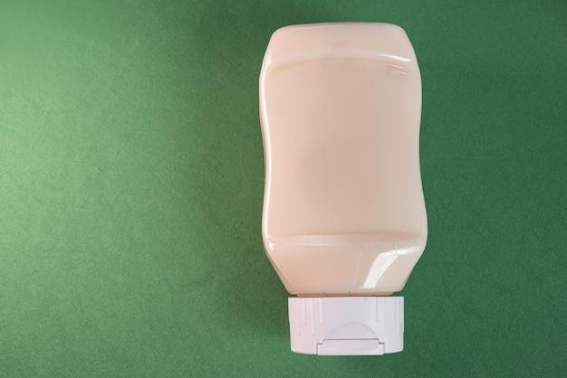 Conteneur de mayonnaise sur la surface verte