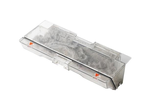 Conteneur plein de poussière pour aspirateur robot isolé sur fond blanc