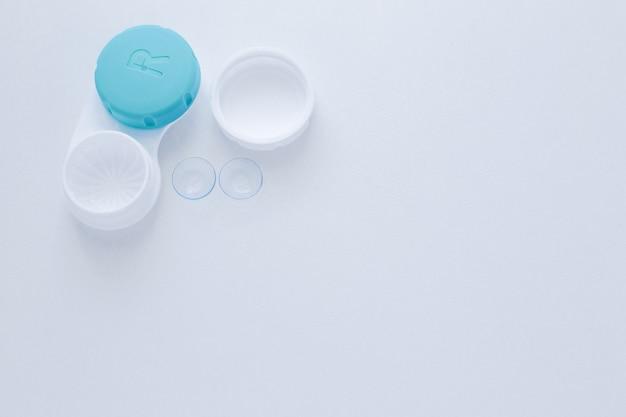 Un conteneur pour lentilles et deux lentilles de contact se trouvent sur le côté sur un fond blanc avec un espace p...