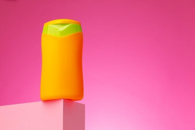 Conteneur de produits de beauté de soins de la peau sur fond rose, espace copie
