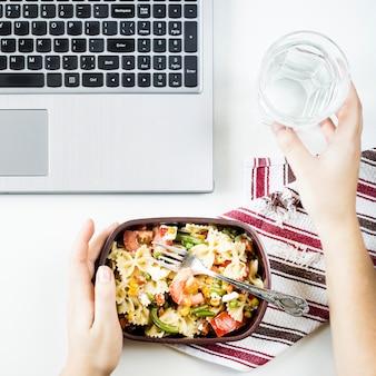 Conteneur avec salade avec des pâtes sur le lieu de travail près de l'ordinateur