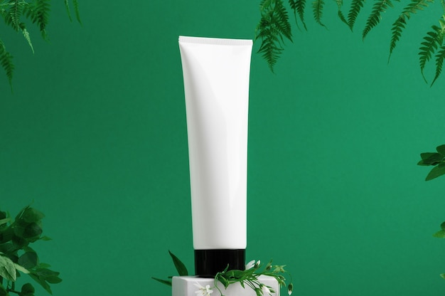 Conteneur sans marque sur la devanture. tube en plastique pour la toilette. feuilles tropicales sur fond. flacon pour la cosmétique professionnelle. espace de copie. produits écologiques et concept de beauté. isolé sur vert.