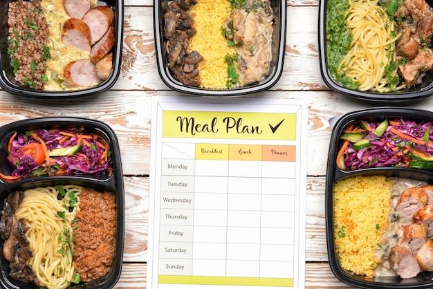 Conteneurs avec des aliments sains et un plan de repas sur bois