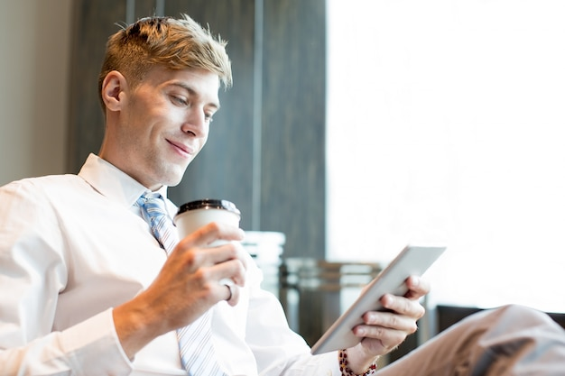 Content business man with cup and tablet