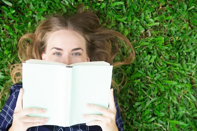 Content girl mentir sur l'herbe et se cacher derrière le livre