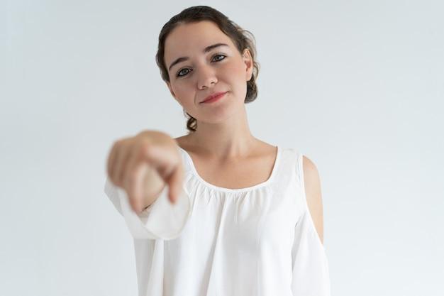 Content jolie femme vous montrant du doigt