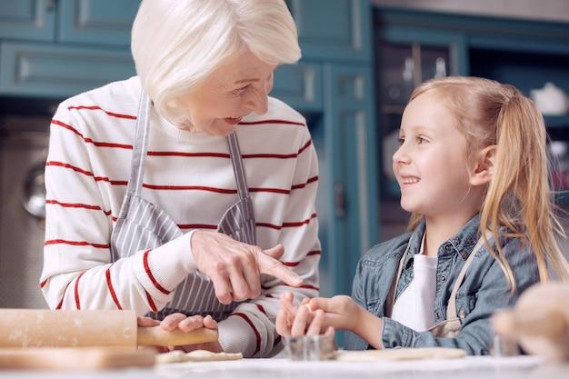 Content avec résultat. enthousiaste femme âgée montrant un petit cookie dans les mains de sa petite-fille et riant pendant qu'ils font tous les deux des cookies ensemble