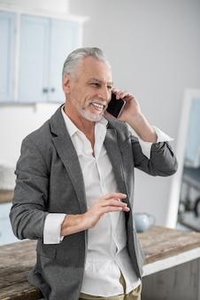 Content de t'entendre. homme barbu attrayant gardant le sourire sur son visage et gesticulant activement tout en passant du temps libre avec plaisir