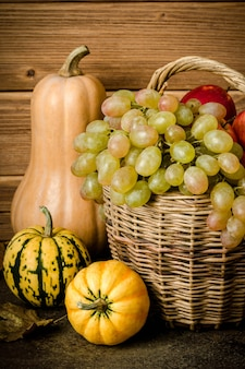 Contenu alimentaire sain, nature morte de courge citrouille, mini citrouilles, panier en osier avec raisins verts et jaunes, pommes rouges, sur une table sombre, fond en bois