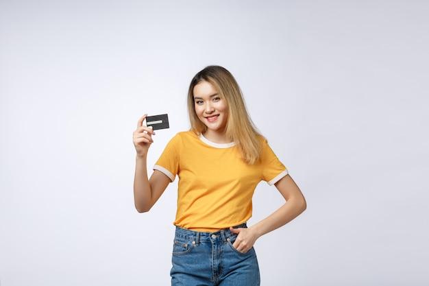 Contenu asiatique woman holding fan de billets en dollars et carte de crédit