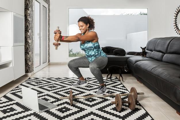Contenu athlète afro-américaine faisant des squats avec des haltères tout en regardant un didacticiel en ligne sur un ordinateur portable pendant l'entraînement à la maison avec des chiens