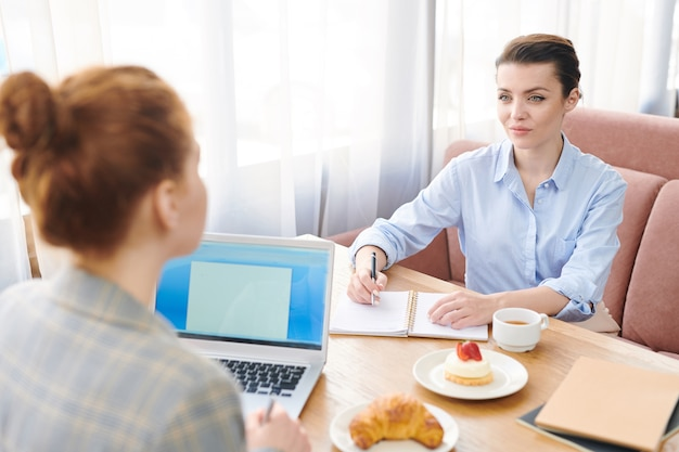 Contenu attrayant brunette businesswoman écrire des idées tout en remue-méninges sur un nouveau projet avec un collègue lors d'une réunion au café