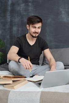 Contenu beau jeune homme assis les jambes croisées sur le lit et regarder des conférences en ligne sur un ordinateur portable tout en profitant de l'enseignement à distance