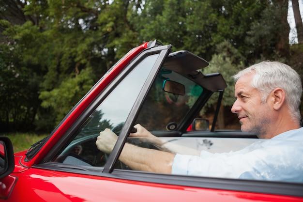 Contenu bel homme conduisant un cabriolet rouge