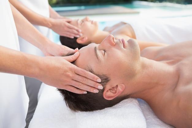 Contenu couple appréciant les massages de la tête près de la piscine