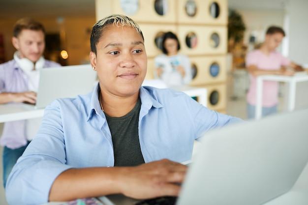 Contenu curieux jeune femme noire en vêtements pour hommes assis à table dans la bibliothèque et à l'aide d'un ordinateur portable tout en faisant des recherches sur internet