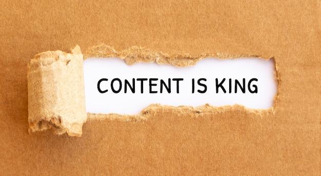 Le contenu du texte est roi apparaissant derrière du papier brun déchiré