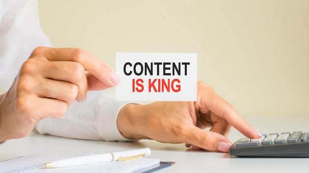 Le contenu est roi, message sur la carte de visite affiché par une femme appuyant sur la touche de la calculatrice sur le lieu de travail dans un bureau léger, mise au point sélective, concept commercial et financier