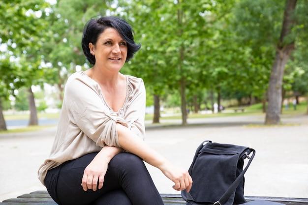 Contenu femme d'âge moyen sur un banc dans le parc