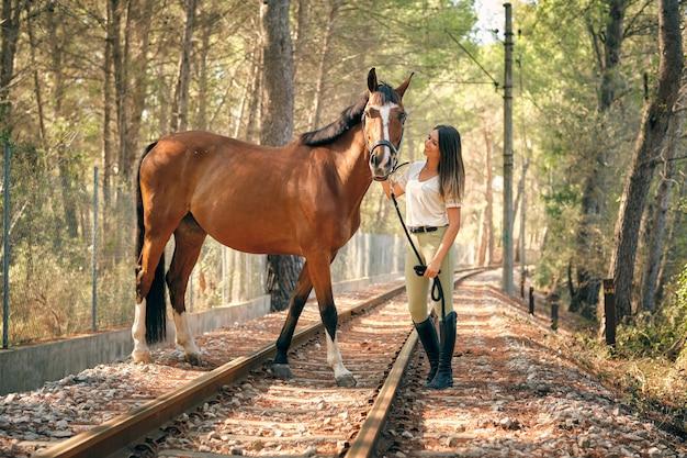 Contenu femme avec cheval dans les bois