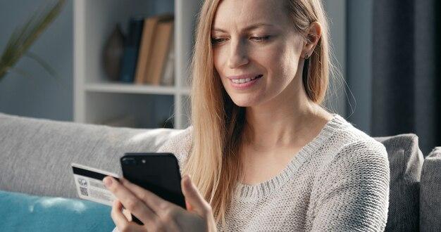 Contenu femme mûre tenant une carte de crédit et à l'aide de smartphone faisant des achats en ligne, mise au point sélective